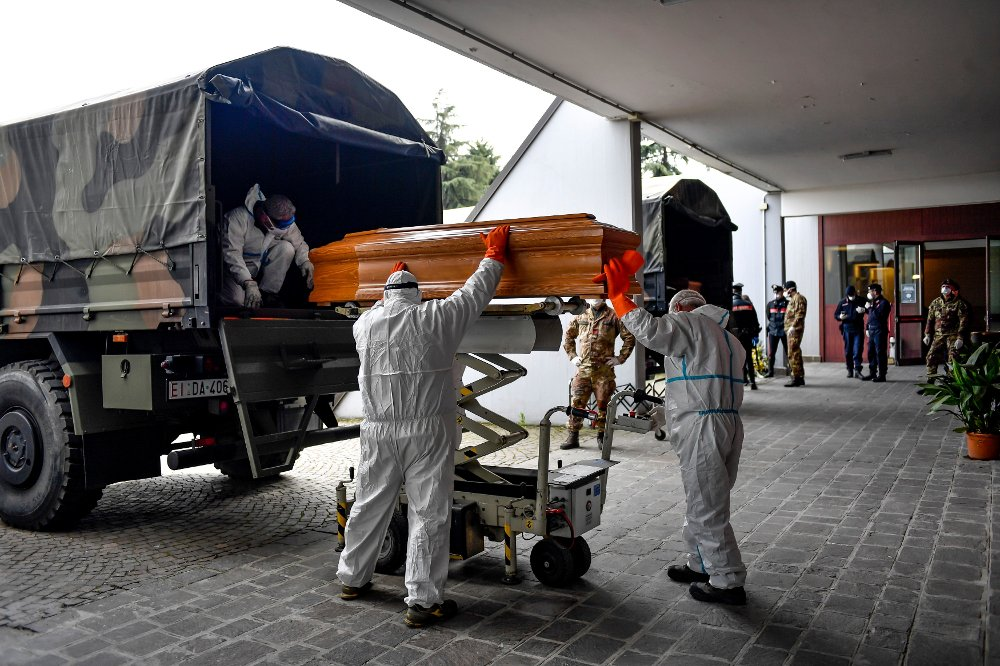 Klikk på bildet for å forstørre. Bilde av lastebil med likkister. Personer laster dem av, og noen står på bakkeplan og tar imot.