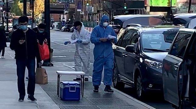 Klikk på bildet for å forstørre. Langs Jackson Avenue i Long Island City, noen minutter fra Manhattan, kan man her se to personer som driver med matlevering. De har på seg full vernedrakt, med både hansker og maske, når de skal levere ut maten.