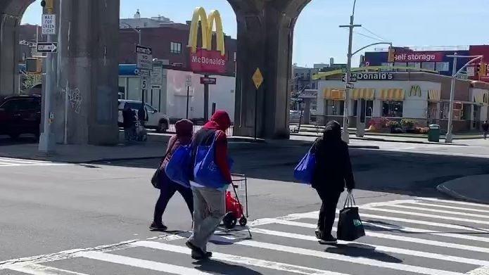 Klikk på bildet for å forstørre. Her går noen fra matkøen i Queens med poser fulle av mat som de har fått inne i matsentralen på menigheten i Queens. På andre siden av gaten ligger Mc Donalds som fortsatt holder åpent for Drive Thru i New York.