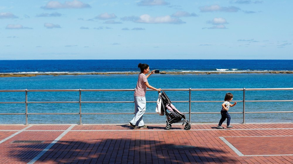 Klikk på bildet for å forstørre. Family members walk at promenade of Las Canteras beach after restrictions were partially lifted for children for the first time in six weeks, following the coronavirus disease outbreak on the island of Gran Canaria, Spain, April 26, 2020. REUTERS/Borja Suarez