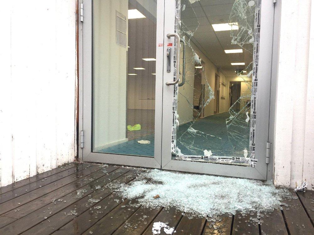 Klikk på bildet for å forstørre. Bildet viser en knust glassdør og mye knust glass rett foran inngangspartiet.