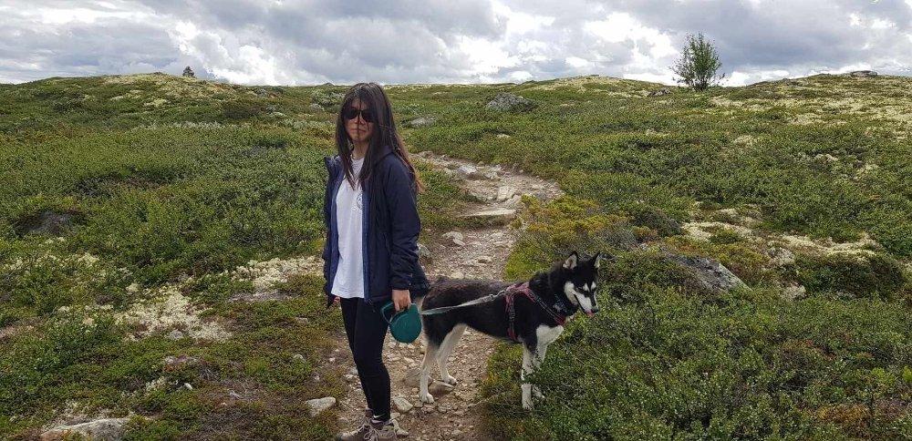 Klikk på bildet for å forstørre. Bilde av avdøde Johanne Zhangjia Ihle-Hansen på fjelltur. Har på seg tynn blå jakke og har hun i bånd. Johanne har på seg solbriller, hvit bluse og svart bukse. Hun har langt svart hår.