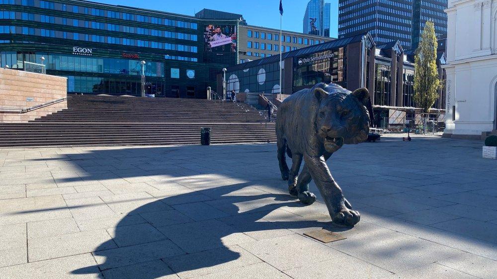 Klikk på bildet for å forstørre. Bilde viser bronsetigeren på Jernbanetorget midt i Oslo sentrum. I bakgrunnen er den åpne plassen ved Oslo S, og inngangspartiet til togstasjonen.