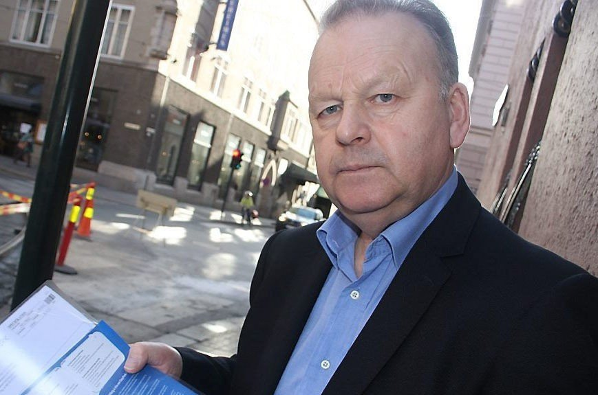 Klikk på bildet for å forstørre. Halvnært bilde av tidligere polititopp Finn Abrahamsen som står med saksdokumenter å hånden og ser i kamera.