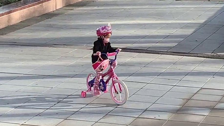 Klikk på bildet for å forstørre. Her sykler en jente med en ansiktsmaske i en park i Queens.
