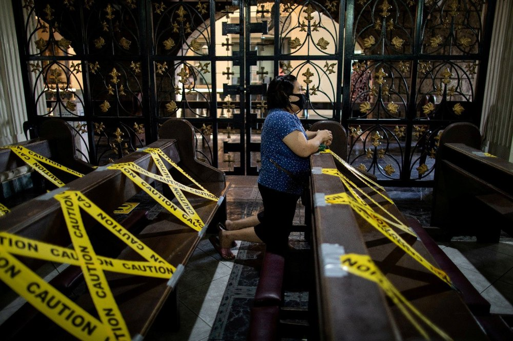 Klikk på bildet for å forstørre. A woman wearing a protective mask kneels to pray in between social distancing markers placed on pews in St. Peter Parish in Quezon City, Metro Manila, Philippines, June 7, 2020. REUTERS/Eloisa Lopez