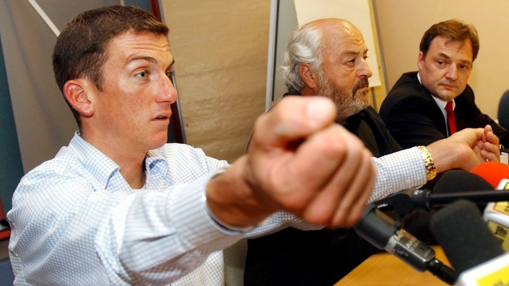 Klikk på bildet for å forstørre. US-cyclist Tyler Hamilton of Swiss team Phonak, left, displays his fists during a press conference in Regensdorf, Switzerland, on Tuesday, Sept 21, 2004. Hamilton is suspected on doping, after doping tests during the Athens 2004 Olympic Games and during the Vuelta allegedly showed evidence of blood from another person.
