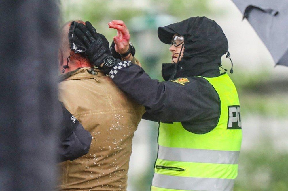 Klikk på bildet for å forstørre. Sian-leder Lars Thorsen geleides bort fra podiet mens det ser ut som han blør fra hodet etter at det brøt ut uroligheter under Sians markering på Festplassen lørdag.