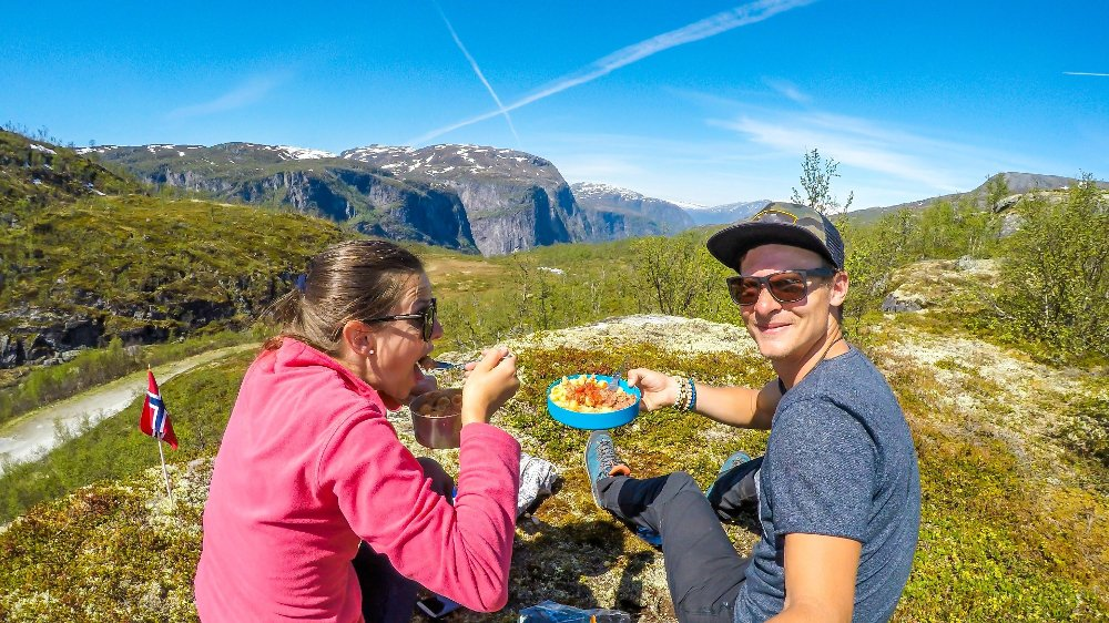 Klikk på bildet for å forstørre. Norway - A young couple preparing meal in the wilderness A couple having a meal in the tall mountains. Girl is eating the noodles with a fork. Boy is holding his portion in one hand, taking selfie with another hand. Camping in Norwegian wilderness.