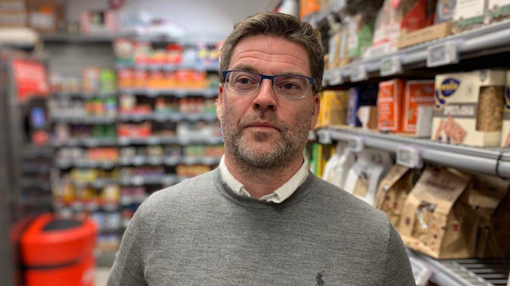 Klikk på bildet for å forstørre. Kommunikasjonssjef i Coop Norge, Harald Kristiansen. Halvnært bilde av ham foran en butikkhylle. Han er iført grå genser og briller.