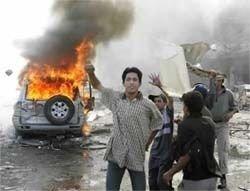 Ungdommer jubler etter at en selvmordsbomber sprengte en konvoi fra irakiske myndigheter i luften i Bagdad 14.6.04.