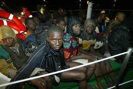 Båtflyktninger søker ly i en Røde Kors-leir etter å ha blitt plukket opp av spansk politi.