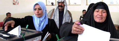To kvinner avgir sin stemme i Bagdad søndag.