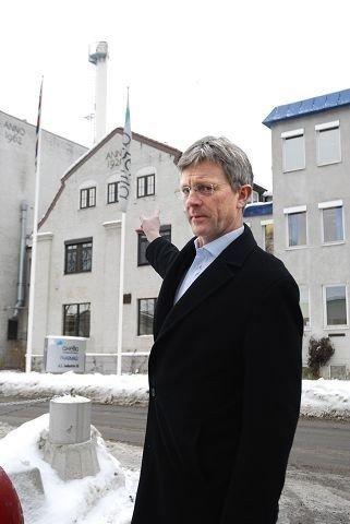 BU-leder Carl Oscar Pedersen peker på utslippspipa og mener at det farmasøytiske selskapet Axellia selv må bære kostnadene for å holde luktforurensingen nede. Foto: Vidar Bakken