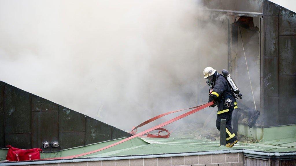 En brannmann forsøker å slukke flammene fra skolen.
