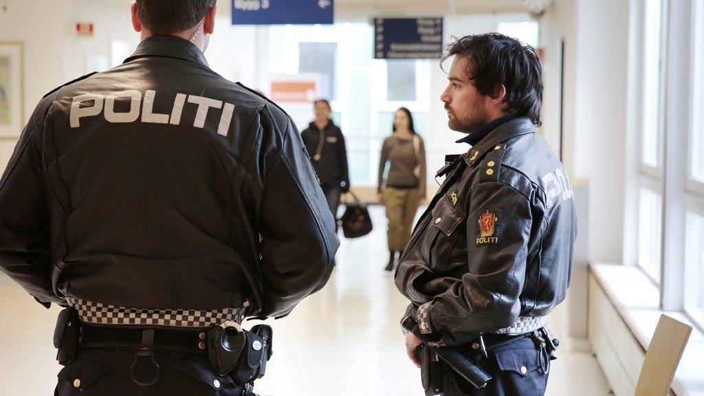 Bevæpnet politi holder holder vakt i en korridor på Ullevål Univeristetssykehus i Oslo hvor to personer ligger hardt skadet etter et oppgjør mellom to rivaliserende romfamilier mandag kveld.