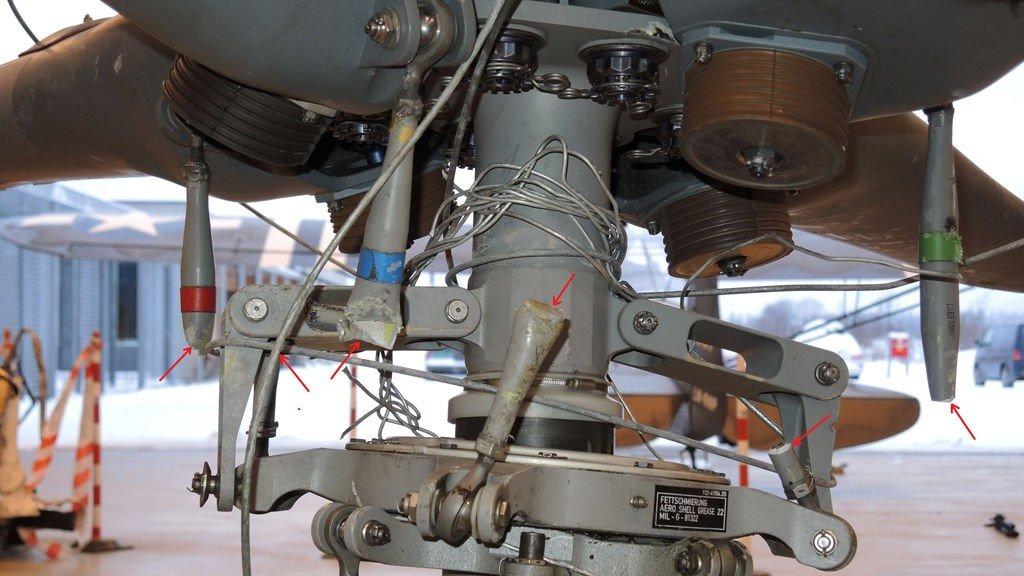 KVEILET RUNDT ROTORMAST: Hovedrotorhodet på ambulansehelikopteret som styrtet ved Sollihøgda tirsdag, fotografert i Havarikommisjonens lokaler på Kjeller i Lillestrøm. De røde pilene markerer bruddene på kontrollstagene som formodentlig oppsto da helikopteret kolliderte med en høyspentledning. Kontrollstagene regulerer vinkelen på rotorbladene. Deler av høyspentledningen sees kveilet rundt rotormasten.