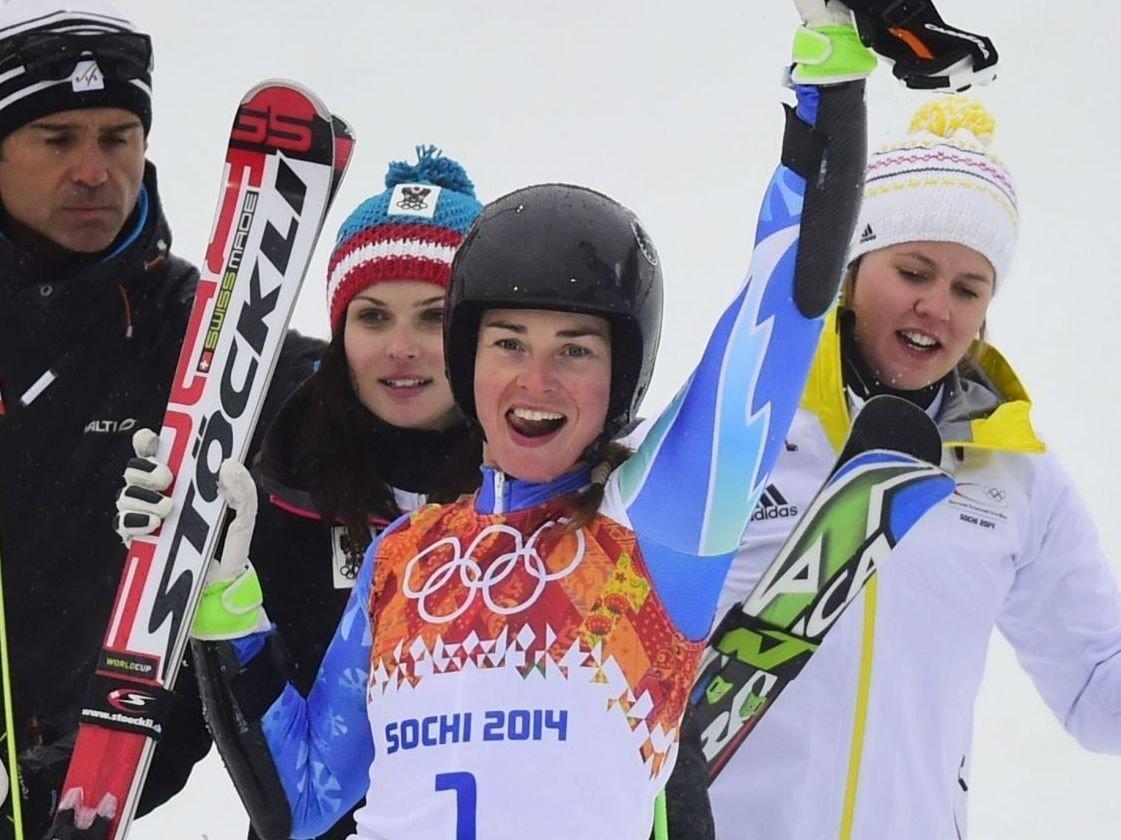 Viktoria Rebensburg fra Tyskland (til høyre) og Anna Fenninger fra Østerrike (til venstre) gratulerer Tina Maze med OL-gullet.