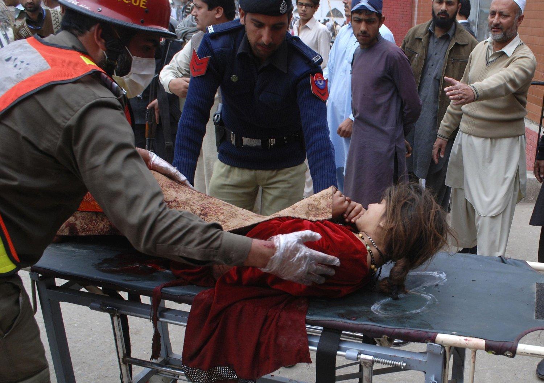 En redningsarbeider og en politimann hjelper en jente som ble skadd i selvmordsangrepet i Peshawar. Mange ble drept i flere bombeangrep i Pakistan fredag.