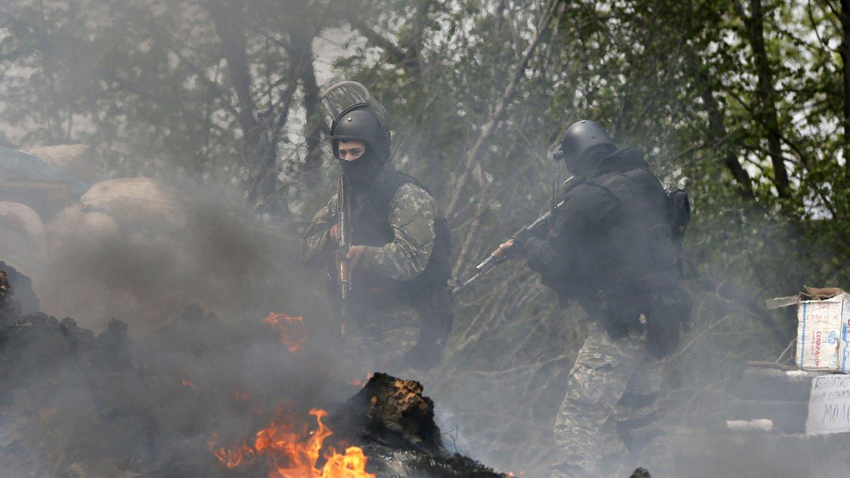 UKRAINSKE SIKKERHETSSTYRKER: Bildet viser ukrainske sikkerhetsstyrker som leter gjennom en veisperring som ble satt fyr på at pro-russiske separatister ved Slavinask 24. april.