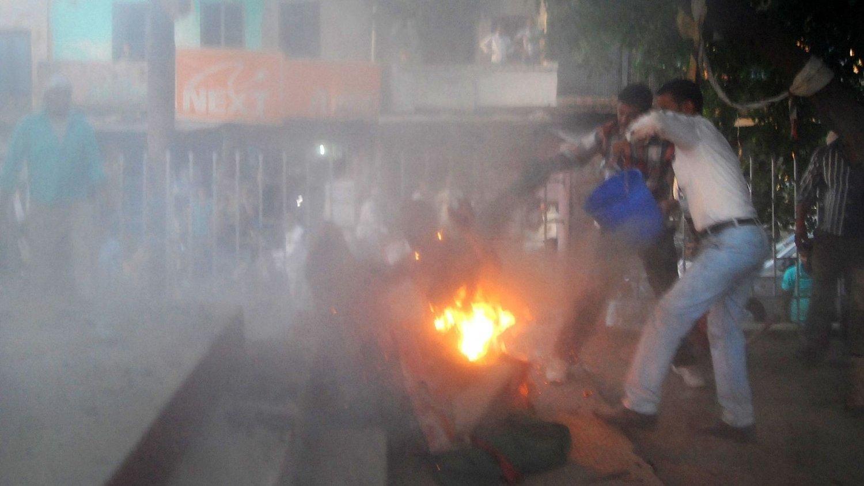SLUKKER: Tilskuere kom løpende til for å slukke den lokale lederen av Bahujan Samaj partiet, Kamruzzama Fauji, og angriperen Durgesh Kumar Singhb da de ble oppslukt av flammene.