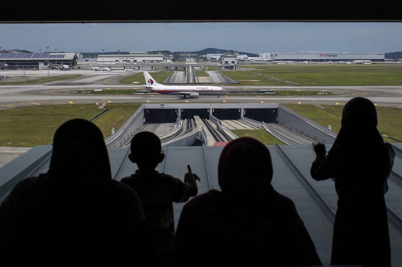 Flypassasjerer avbildet mens de står og titter ut mot et passasjerfly fra Malaysia Airlines som takser på rullebanen på den internasjonale flyplassen i Kuala Lumpur. 239 mennesker var om bord i MH370-flyet da det forsvant sporløst for over hundre dager siden.