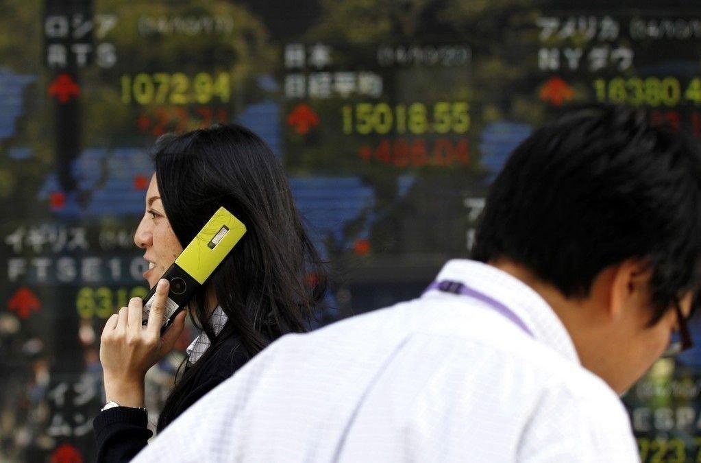 En fotgjenger snakker i mobilen i det hun passerer en elektronisk børstavle utenfor et meglerkontor i Tokyo.