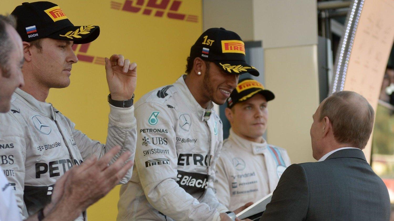 AVGJORDE I RUSSLAND: Lewis Hamilton mottar trofeet fra Russlands president Vladimir Putin etter seieren sist helg. Til venstre ser vi Nico Rosberg, som ble nummer to i Russland Grand Prix i Sotsji.