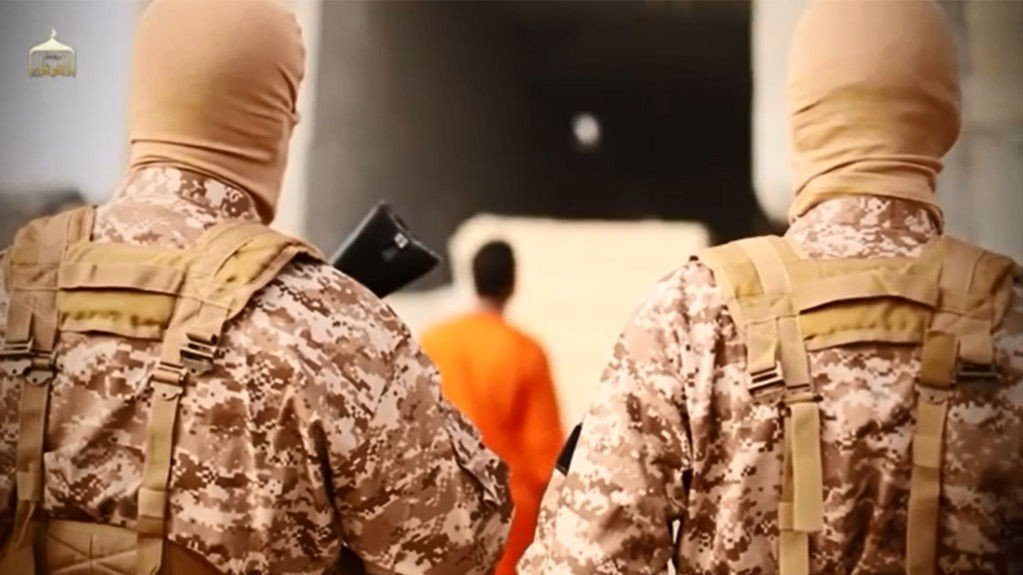 Stillbildet er hentet fra den grufulle videoen til IS, og viser den jordanske piloten som er kledd i oransje i bakgrunnen.