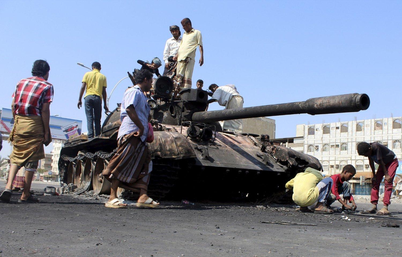 STRIDSVOGN: Folk har samlet seg ved en utbrent stridsvogn i den jemenittiske havnebyen Aden mandag.