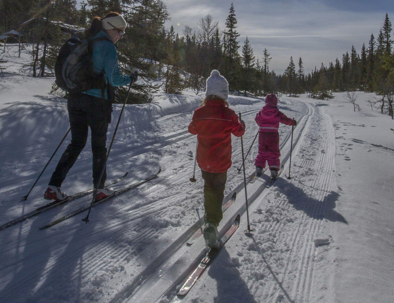 Blå Himmel, hvit snø og mor og to døtre på skitur.