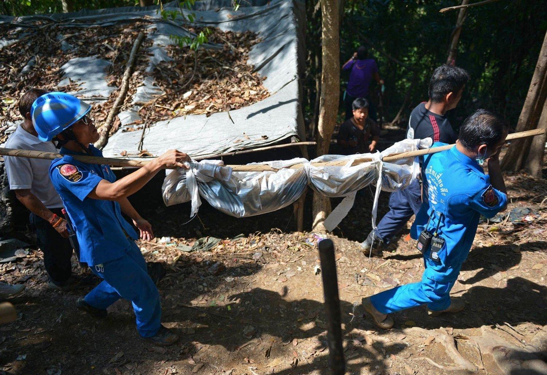 MASSEGRAV: Krimteknikere bærer bort en av de døde, funnet i en massegrav ved en forlatt leir i jungelen.
