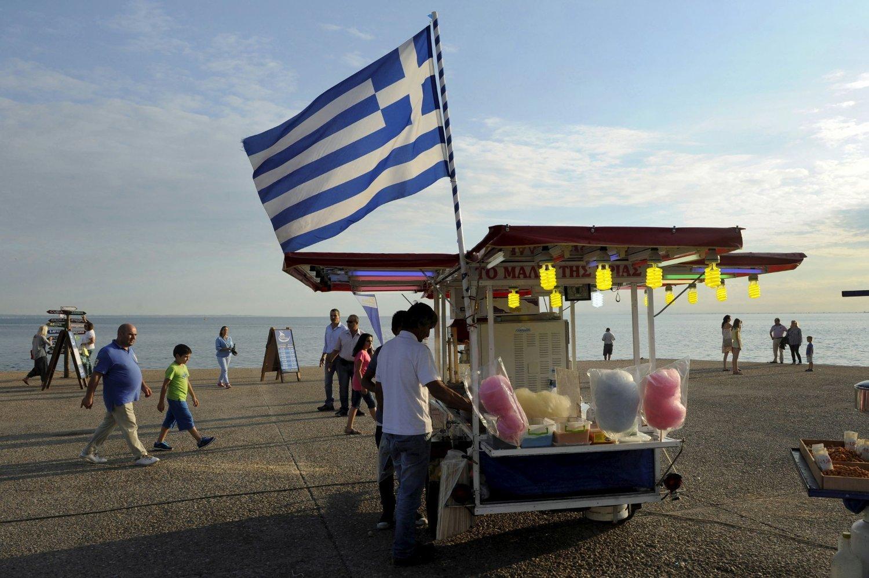Det greske flagget er plassert på en bod som selger sukkerspinn i den nordlige byen Thessaloniki i Hellas onsdag. Samme dag oppfordret landets statsminister grekerne til å stemme nei til låneavtalen med EU søndag.