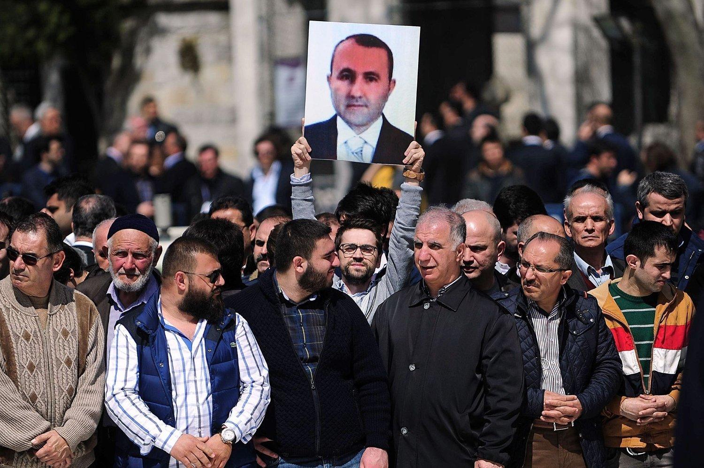 DREPT: En mann holder opp et portrett av den drepte Mehmet Selim Kiraz under begravelsen i Istanbul 1. april.