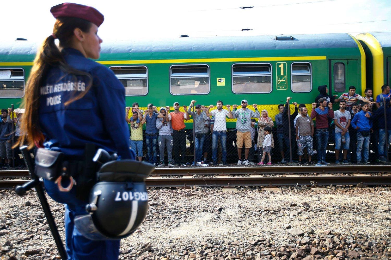 Ungarsk politi står vakt ved et tog der flyktninger protesterer mot å bli overført til en leir for å registreres i stedet for å få reise videre til Østerrike.
