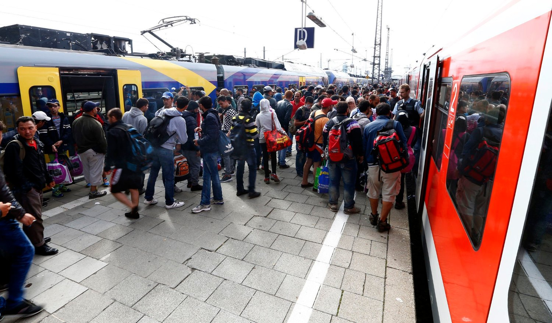 lyktninger og migranter venter på å gå om bord på et regionaltog på togstasjonen i München. Tyskland har søndag midlertidig gjeninnført grensekontroll på grensen til Østerrike på grunn av den store tilstrømmingen av flyktninger til landet.