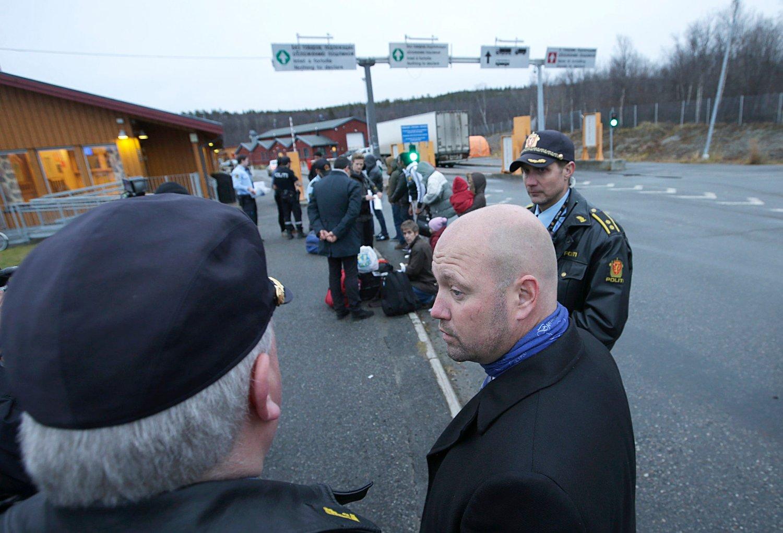 JUSTISMINISTER Anders Anundsen besøker Storskog utenfor Kirkenes. Her står han rett ved grensa inn til Norge. En gruppenflyktninger står rett bak justisministeren. (T.h) operasjonsleder i Østfinnmark politidistrikt Svein Erik Jakobsen.