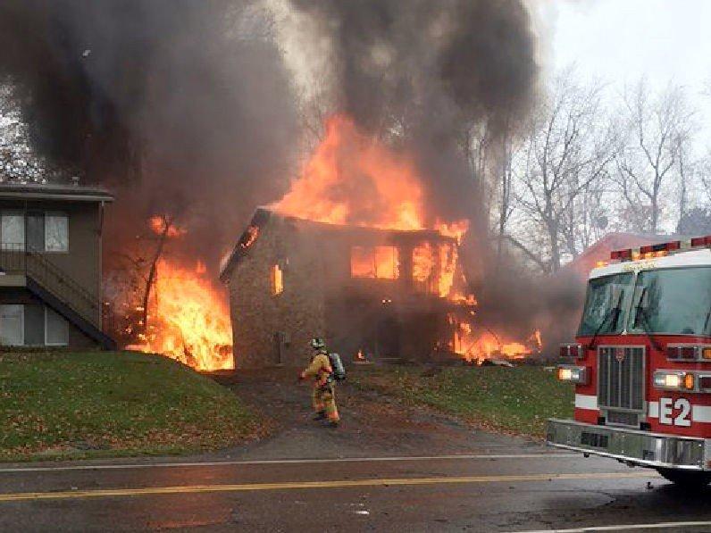 En brannmann forsøke rå slukke flammene i et hus, etter at et småfly styrtet inn i bygningen i Akron, Ohio tirsdag kveld, lokal tid.