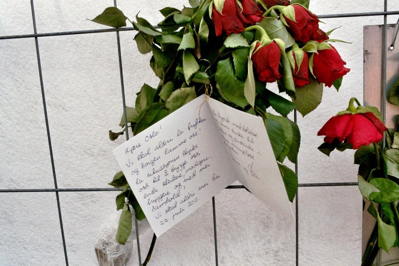 Roser på sperring i Grubbegata 25. juli 2011. På kortet står følgende tekst: «Vi skal aldri la frykten og sorgen lamme oss! La situasjonen styrke oss til å bygge oss enda sterkere, modigere, tryggere og med mer samhold! Vi skal aldri mer ha 22. juli 2011».