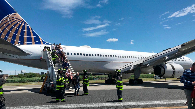 EVAKUERT: Her blir passasjerene ombord et United Airlines-fly evakuert etter at flyet skled av rullebanen.