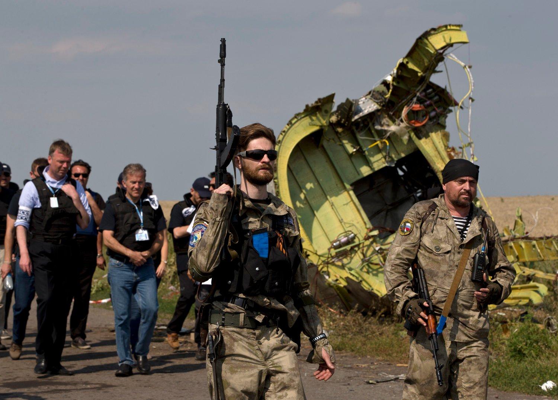 Arkivbilde fra 22. juli 2014 hvor en prorussisk opprører passerer medlemmer av OSSE ved vraket av Malaysia Airlines MH17 som var blitt skutt ned over Ukraina fem dager tidligere. Onsdag ble tre russere og en ukrainer siktet for å stå bak nedskytingen av passasjerflyet. Foto: Vadim Ghirda/ AP / NTB scanpix