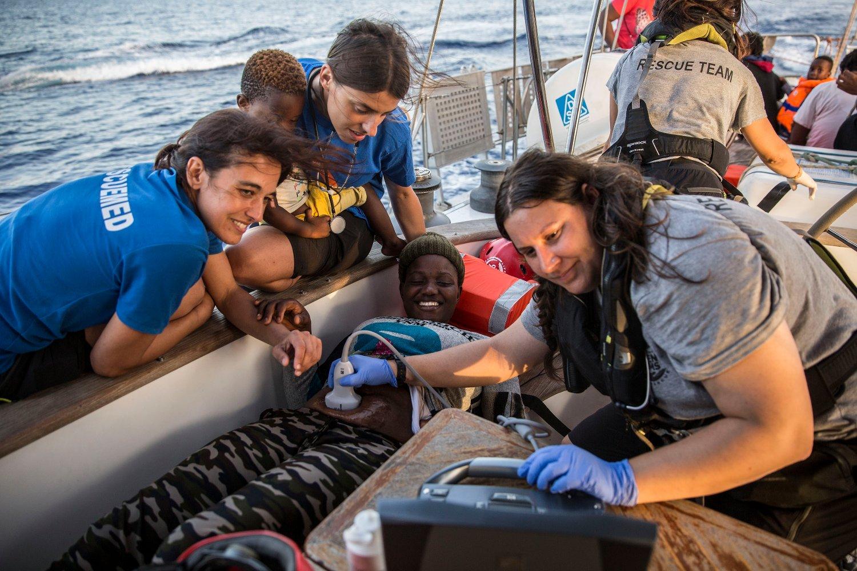 83cbb1f3 Leger hjelper en gravid kvinne om bord på det italienske skipet som  allerede ligger utenfor Lampedusa