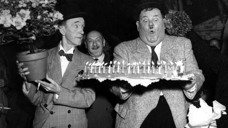TYKK OG TYNN: Stan Laurel, den lille og spinkle Halvan, og Oliver Hardy, den store og smilende Helan, gjorde stor suksess som komikere. Her er de fotografert i Billancourt i Frankrike på Helans 58-årsdag.