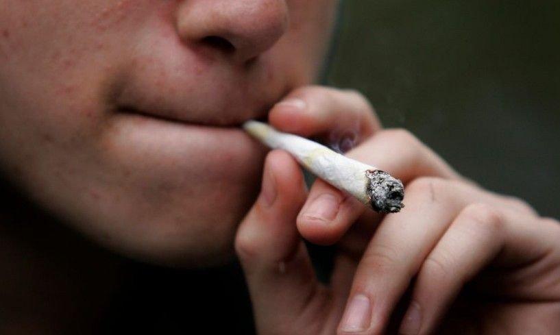 Utsnitt av ansiktet på mann som røyker hasj.
