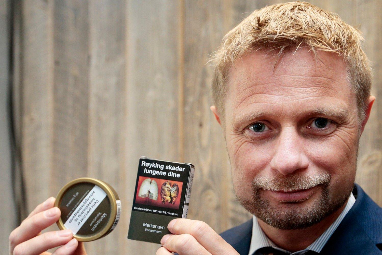 Bent Høie i portrett som holder opp en snusboks og en røykpakke.