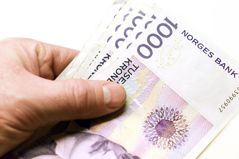 En hånd som holder i sedler av norske tusenlapper.