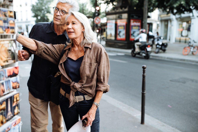 Pensjonert par som ser på postkort på ferietur.
