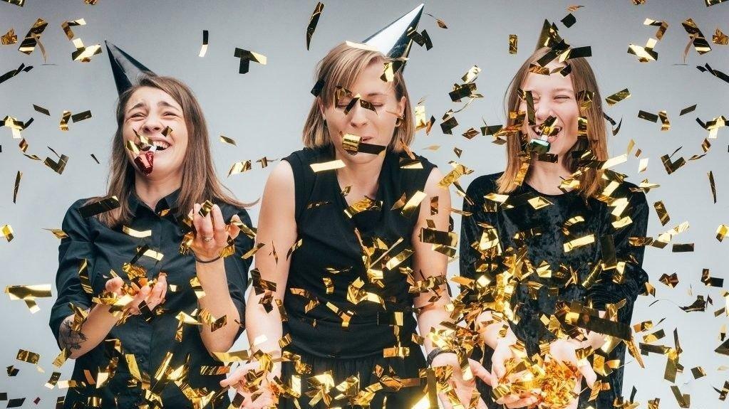 Tre kvinner med konfetti.