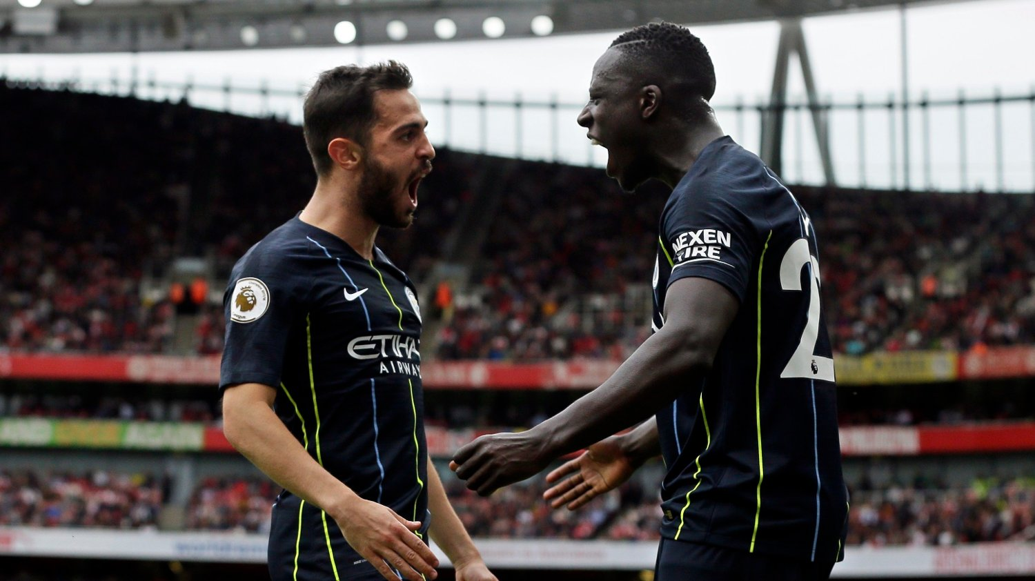 Manchester City's Bernardo Silva celebrates with teammate Benjamin Mendy, right, after scoring his side's second goal during the English Premier League soccer match between Arsenal and Manchester City at the Emirates stadium in London, England, Sunday, Aug. 12, 2018.