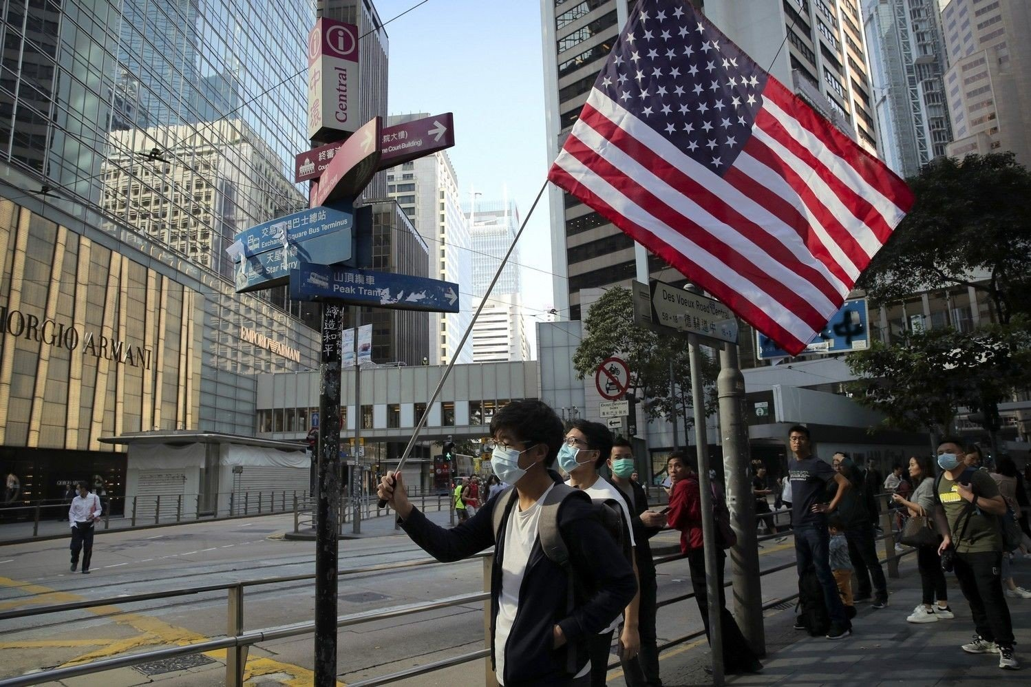 Hong Kong Protests A protester holds an American flag during a demonstration in the financial district in Hong Kong, Wednesday, Nov. 20, 2019. Hong Kong schools reopened Wednesday after a six-day shutdown but students and commuters faced transit disruptions as the last protesters remained holed up on a university campus.